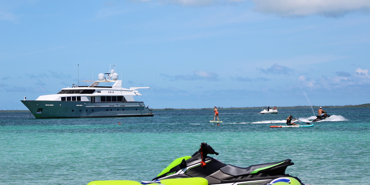 ODIN 126' Trinity, waverunners and paddleboards in the background; a waverunner in the foreground.